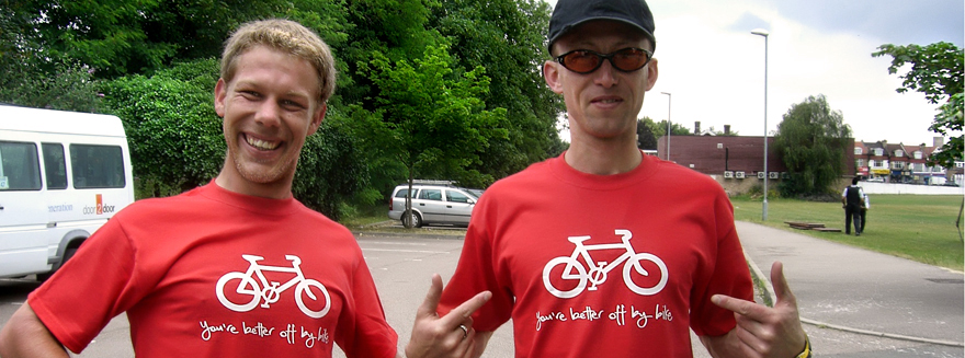 Two Bugbugs riders showing off their T-Shirts, with the slogan 'you're better off by bike'