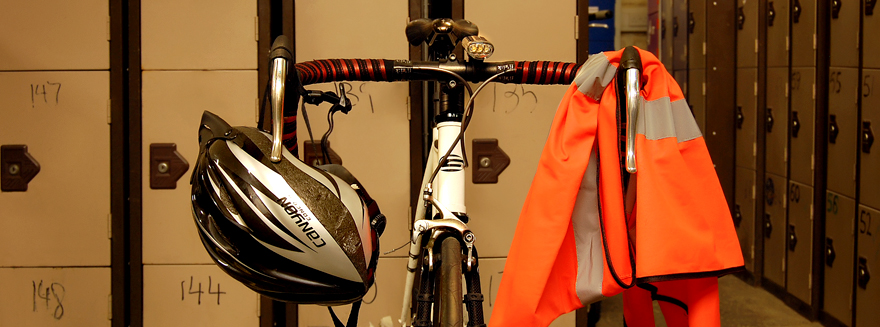 Featuring a bike's handlebars, high visibility safety vest and helmet in front of lockers - to denote Bugbugs training